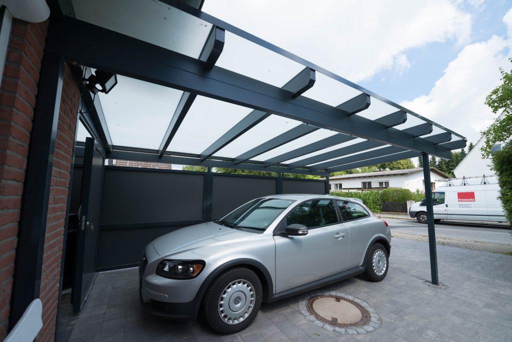 Glas Carport mit Milchglas und Pultdach vom Hersteller Schulze Braak aus Hamburg. Das Auto Carport hat eine Holz-Konstruktion und wurde in der Farbe anthrazit, grau gestrichen.