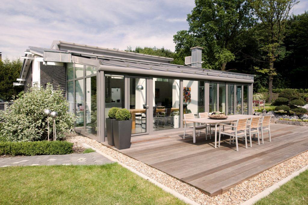 Solarlux Wintergarten aus Aluminium in grau mit Pultdach und integrierter Beschattung an einem Einfamilienhaus. Erhältlich beim Solarlux Händler Schulze Braak bei Hamburg.