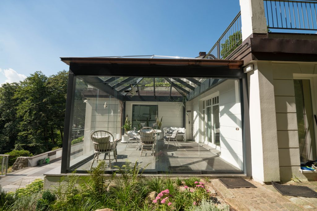 Holz Sommergarten in Grau mit Walmdach aus Hamburg. Hergestellt und gebaut von Schulze Braak. Integriert in eine innenliegende Hausecke und Ganzglas Schiebetüren. Ohne Dachüberstand.